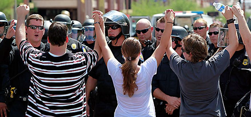 Protesters join hands as police block the street Thursday, July 29, 2010 in Phoenix during a rally against Arizona's new immigration law, SB1070. Opponents of Arizona's immigration crackdown went ahead with protests Thursday despite a judge's ruling that delayed enforcement of most the law. (AP Photo/Matt York)