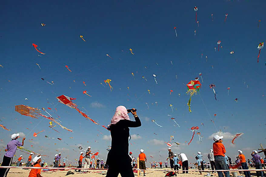 Thousands of Palestinian children in Beit Lahiya, Gaza Strip, fly kites in an attempt to break the world record for the number of kites flying simultaneously. More than 7,200 kites were raised into the air on Thursday, July 29, 2010, setting a new world record in an event sponsored by the United Nations. (AP Photo/Khalil Hamra)