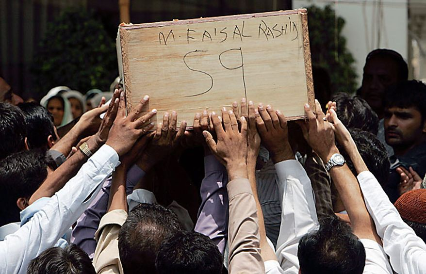 The casket of a plane crash victim is carried during a funeral prayer in Karachi, Pakistan, on Thursday, July 29, 2010. The Airbus A321 operated by Pakistani carrier Airblue crashed into hills overlooking the country's capital, Islamabad, during stormy monsoon weather, killing all 152 people on board. (AP Photo/Karachi)