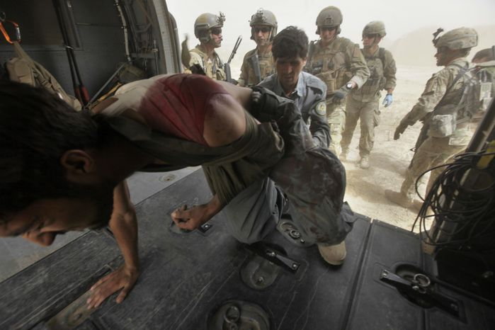 An Afghan National Police officer helps his fellow officer on to a U.S. Air Force rescue helicopter after he was shot during combat with the Taliban, in the Arghandab Valley, Kandahar province, southern Afghanistan, Thursday July 29, 2010. Rescue teams are one part of the U.S. Air Force's 451st Air Expeditionary Wing in southern Afghanistan. (AP Photo/Brennan Linsley)