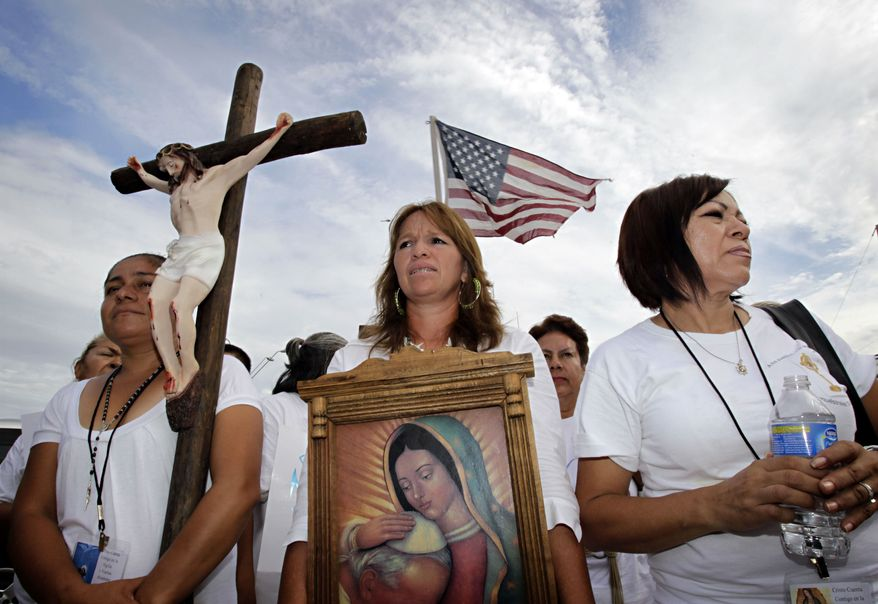 From left, Maria Duran, Maria Uribe and Giornia Sanchez march in protest Thursday, July 29, 2010, in Phoenix to rally against Arizona's new immigration law, SB1070. Opponents of Arizona's immigration crackdown went ahead with protests Thursday despite a judge's ruling that delayed enforcement of most the law. (AP Photo/Matt York)