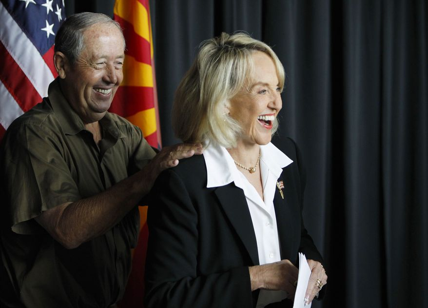 Arizona Republican Gov. Jan Brewer, right, smiles as Max Wilson, Maricopa County Board of Supervisors representing District 4, pats the governor on the back at a news conference in Glendale, Ariz., Friday, July 30, 2010. Brewer and Arizona Sen. John McCain held the news conference in the Phoenix suburb of Glendale to applaud a U.S. Air Force decision to base new F-35 combat jets at Luke Air Force Base in Glendale, but the event abruptly ended when the barrage of questions were regarding the Arizona immigration law and the next steps the governor was taking in the court battle. (AP Photo/Ross D. Franklin)