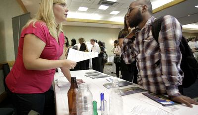In this July 20, 2010, photo, Haley Wright, left, a human resources professional with Plastipak Packaging Inc., meets with a prospective job applicant during a National Career Fairs Job Fair in Plano, Texas. New jobless claims fell last week for the third time in four weeks, but remain above 450,000, where they have been all year. (AP Photo/Tony Gutierrez)