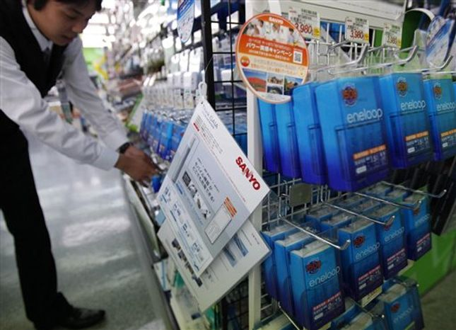 A salesclerk adjusts Sanyo's eneloop rechargeable batteries on display at Yamada Denki LABI electric shop in Tokyo, Thursday, July 29, 2010. Panasonic is planning to take 100 percent ownership of its subsidiaries Sanyo Electric and Panasonic Electric Works in a move costing up to $9.4 billion to strengthen green businesses such as electric cars and solar panels. (AP Photo/Shuji Kajiyama)