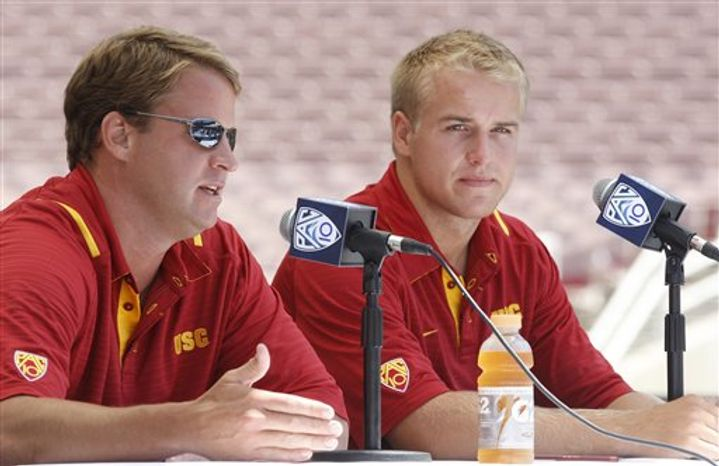 Southern California football coach Lane Kiffin, left, and quarterback  Matt Barkley speak to reporters during the Pac-10 Football Media Day at the Rose Bowl in Pasadena, Calif, on Thursday, July 29, 2010.  (AP Photo/Damian Dovarganes)