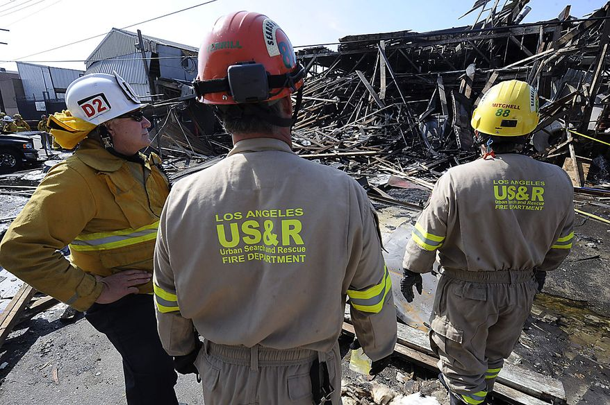 Members of the Los Angeles Fire Department urban search and rescue team survey damage after a suspected natural gas explosion at a welding shop collapsed part of the building and hurled two workers into the street, killing one and leaving the other in critical condition, Friday, July 30, 2010, in Los Angeles. (AP Photo/Gus Ruelas)