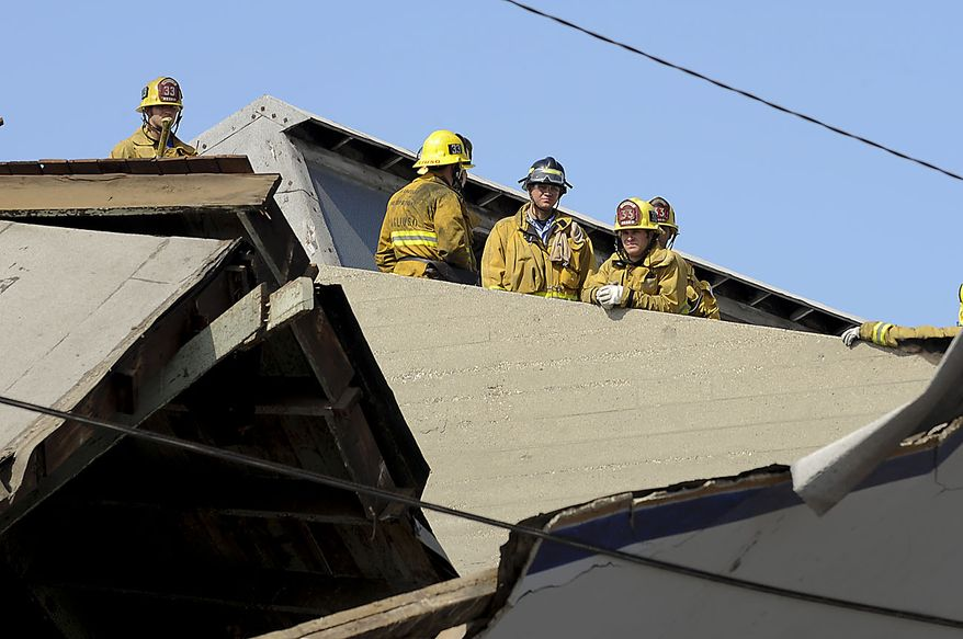 Members of the Los Angeles Fire Department survey damage from a nearby rooftop after a suspected natural gas explosion at a welding shop collapsed part of the building and hurled two workers into the street, killing one and leaving the other in critical condition, Friday, July 30, 2010, in Los Angeles. (AP Photo/Gus Ruelas)
