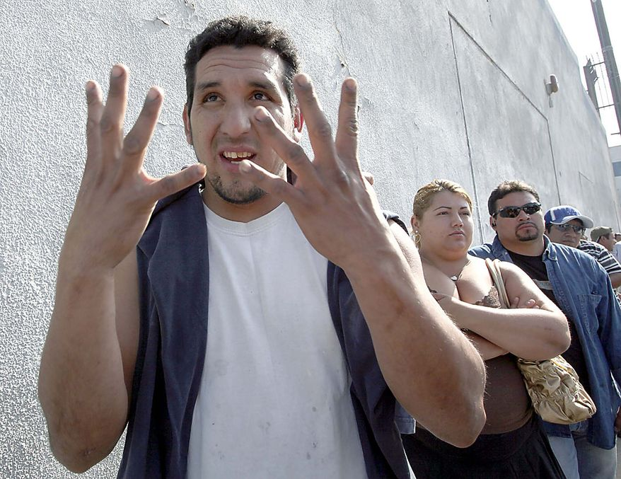 Daniel Ibarra, left, gestures while speaking about a suspected natural gas explosion Friday July 30, 2010 in Los Angeles. The explosion collapsed part of the building and hurled two workers into the street, killing one and leaving the other in critical condition, fire officials said. (AP Photo/Nick Ut)