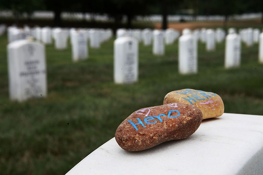 """Stones with the word """"hero"""" written on them lay on a grave stone in Section 60, where many soldiers from the Iraq and Afghanistan wars are buried, Thursday, July 29, 2010, at Arlington National Cemetery in Arlington, Va. Estimates of the number of graves that might be affected by mix-ups at Arlington National Cemetery grew from hundreds to as many as 6,600 on Thursday, as the cemetery's former superintendent blamed his staff and a lack of resources for the scandal that forced his ouster.  (AP Photo/Jacquelyn Martin)"""