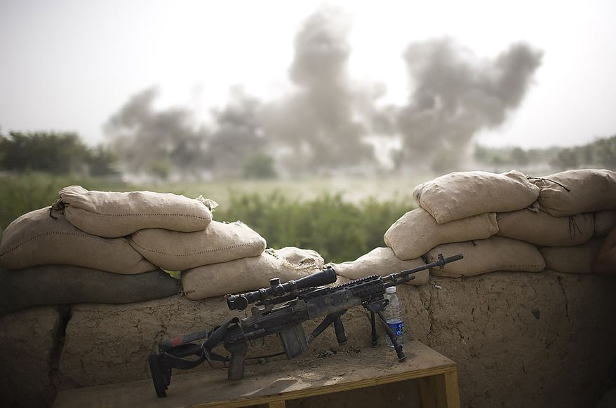 An M-14 sniper rifle sits beside a watch tower as smoke rises in the background after U.S. soldiers blew up a mud wall which Taliban insurgents were using as cover to attack troops from the 1-320th Alpha Battery, 2nd Brigade of the 101st Airborne Division at Combat Outpost Nolen, in the volatile Arghandab Valley, Kandahar, Afghanistan, Thursday, July 29, 2010. (AP Photo/Rodrigo Abd)