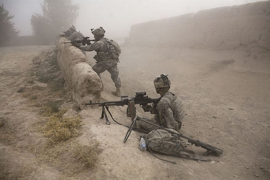 U.S. soldiers stand guard as a medical helicopter arrives to evacuate a soldier from 1-320th Alpha Battery, 2nd Brigade of the 101st Airborne Division, who was seriously wounded when he stepped on an improvised mine near Combat Outpost Nolen, in the volatile Arghandab Valley, Kandahar, Afghanistan, Friday, July 30, 2010. (AP Photo/Rodrigo Abd)