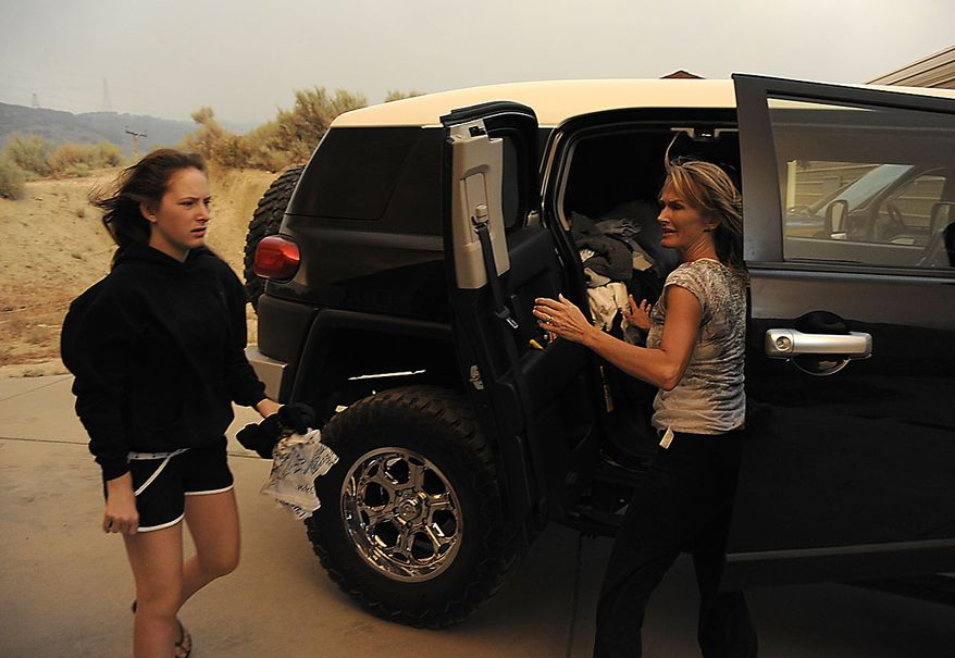 Two unidentified women load a car with their belongings as flames approach their home from a fast moving wildfire near Palmdale, Calif., on Thursday, July 29, 2010. (AP Photo/Dan Steinberg)
