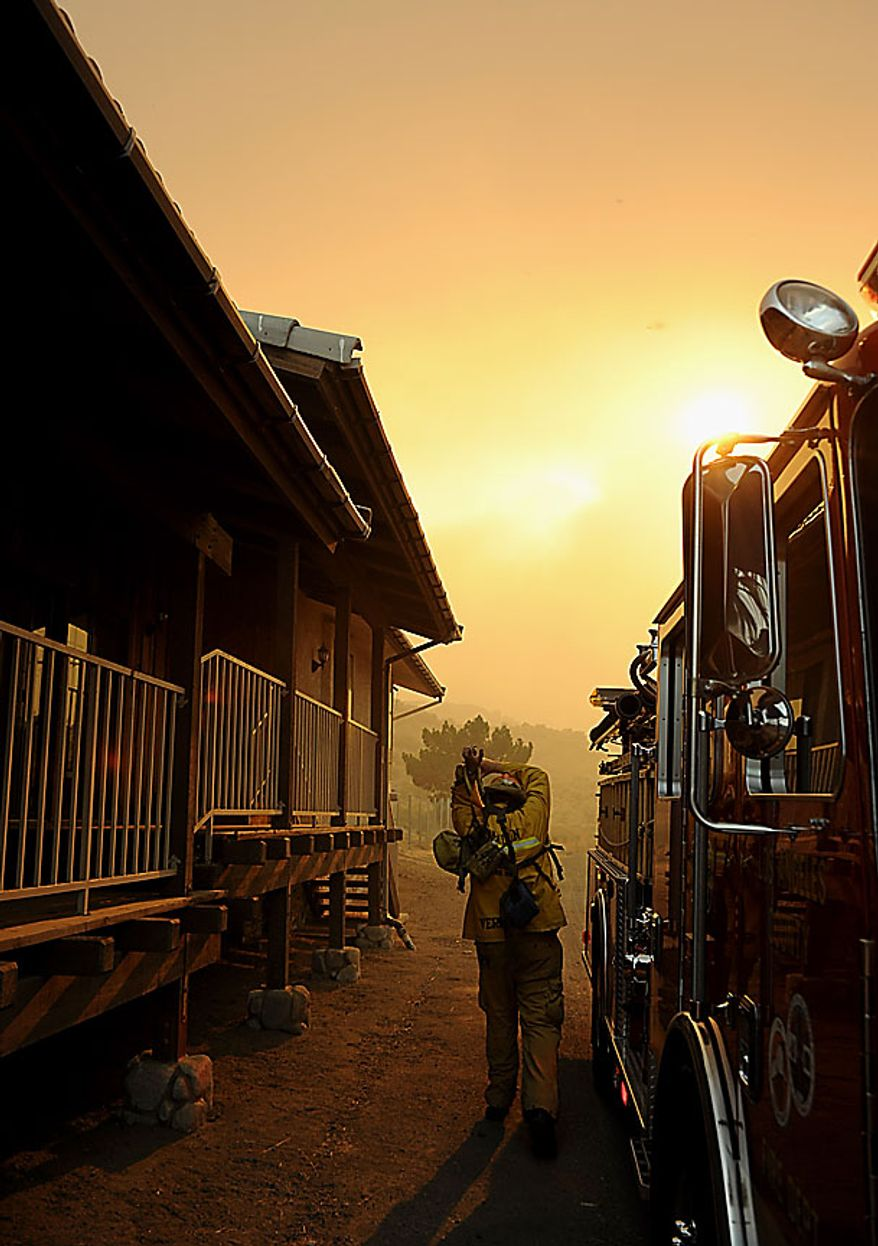 A firefighter dons his gear as a fast moving wildfire burns near Palmdale, Calif., on Thursday, July 29, 2010. (AP Photo/Dan Steinberg)