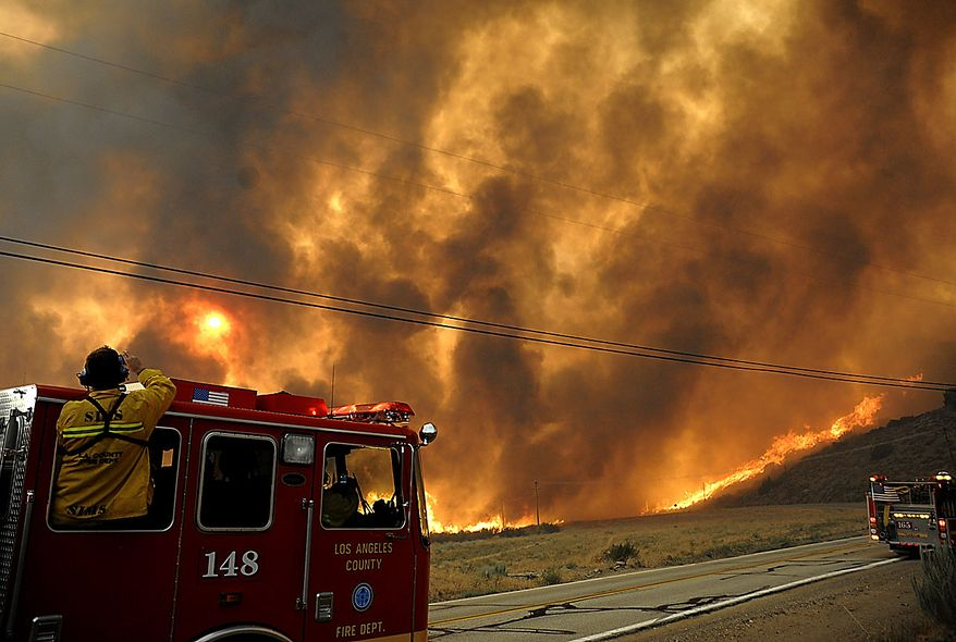 A firefighter looks on as a fast moving wildfire approaches Elizabeth Lake Road in the Leona Valley near Palmdale, Calif. on Thursday, July 29, 2010. Mandatory evacuations were issued for the community of Leona Valley on Thursday evening, Los Angeles County Fire Inspector Matt Levesque said. (AP Photo/Dan Steinberg)