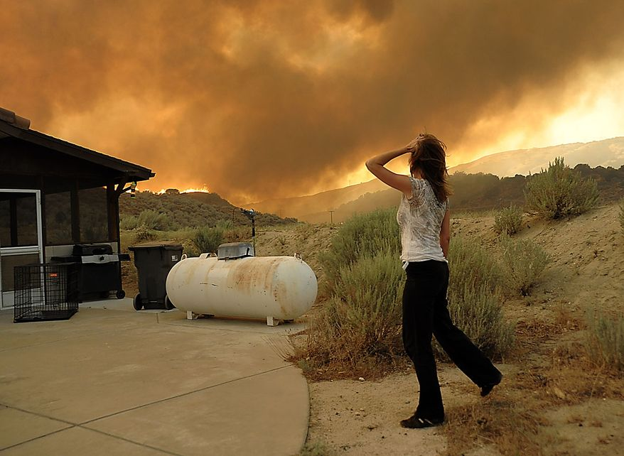 An unidentified woman watches as flames approach her home from a fast moving wildfire near Palmdale, Calif. on Thursday, July 29, 2010. (AP Photo/Dan Steinberg)