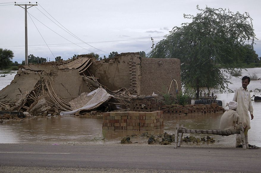Pakistani villagers gather beside their house that collapsed in heavy monsoon rainfall on the outskirts of Dera Ismail Khan, Pakistan, Thursday, July 29, 2010. (AP Photo/Ishtiaq Mahsud)