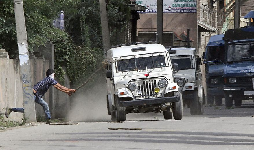 A Kashmiri protester attacks an Indian police vehicle during a protest in Srinagar, India, Friday, July 30, 2010. Massive clashes erupted in Indian Kashmir's main city Friday after two men were wounded as paramilitary soldiers fired on a group of anti-India protesters, police and locals said. (AP Photo/Mukhtar Khan)