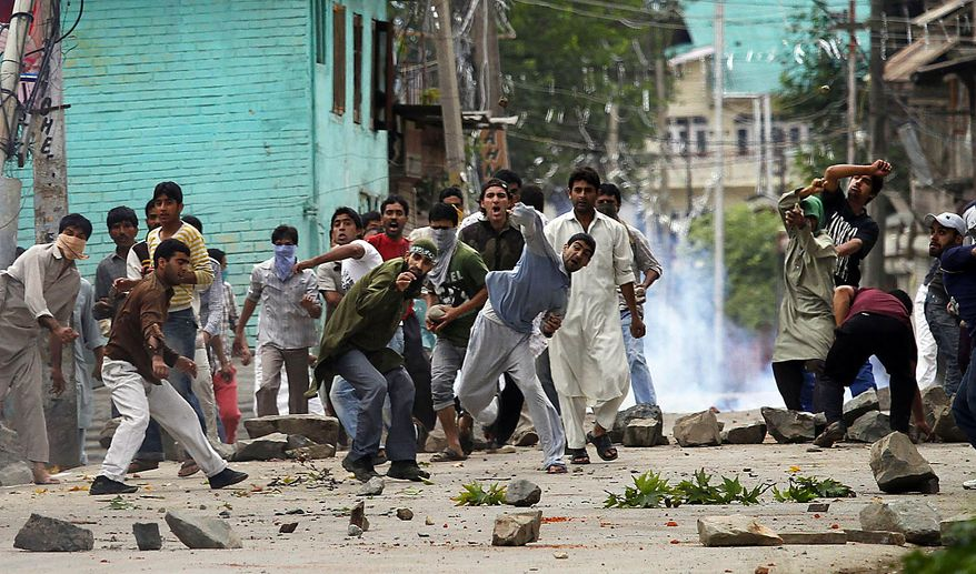 Kashmiri Muslim protesters throw rocks and bricks at Indian police officers during a protest in Srinagar, India, Friday, July 30, 2010. Massive clashes erupted in Indian Kashmir's main city Friday after two men were wounded as paramilitary soldiers fired on a group of anti-India protesters, police and locals said. (AP Photo/Dar Yasin)