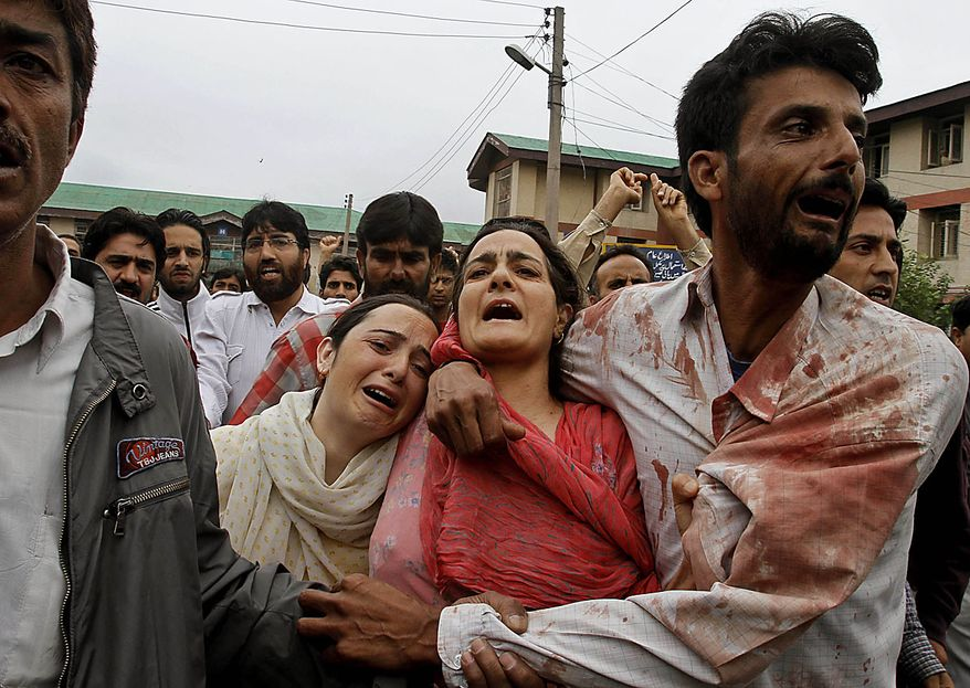 Relatives of Iqbal Khan, one of the wounded civilians, wail outside a hospital in Srinagar, India, Friday, July 30, 2010. Massive clashes erupted in Indian Kashmir's main city Friday after two men were wounded as paramilitary soldiers fired on a group of anti-India protesters, police and locals said. Khan was in critical condition in a hospital. (AP Photo/Mukhtar Khan)