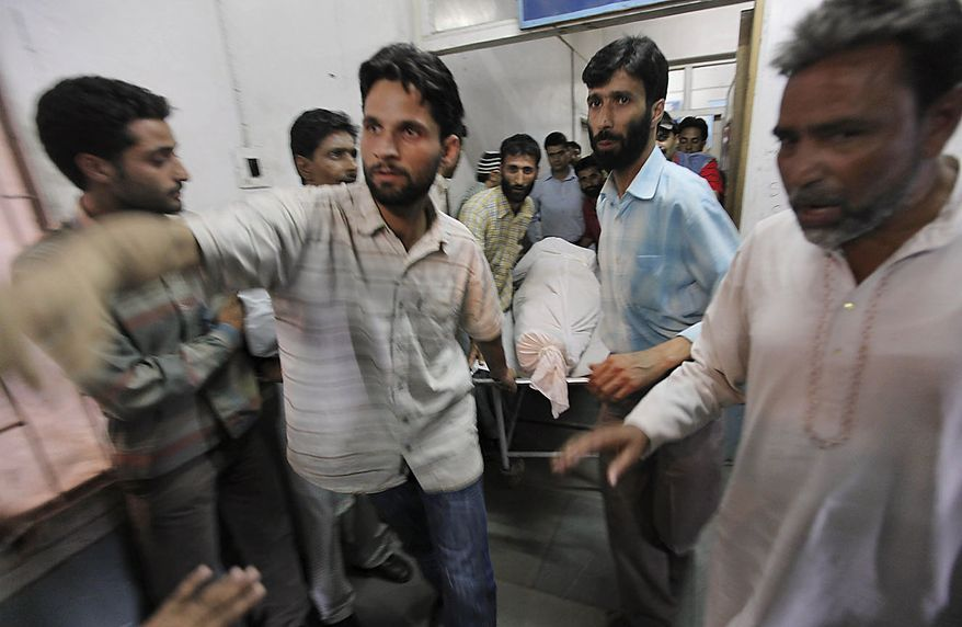 Paramedics carry the body of Showket Ahmad on a stretcher inside a local hospital in Srinagar, India, Friday, July 30, 2010. Paramilitary soldiers fired on hundreds of demonstrators in Indian Kashmir on Friday, killing two men and wounding at least 12 others, police said as protests against Indian rule spread across the region. Showket was one of two civilian killed during a protest in Sopore, some 50 Kilometers (31 miles) northwest of Srinagar. (AP Photo/Dar Yasin)