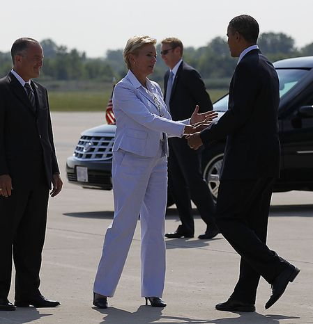 Michigan Gov. Jennifer Granholm, center, and her husband Daniel Mulhearn, left, greet President Barack Obama upon his arrival at Detroit Wayne County Airport in Detroit, Friday, July 30, 2010. (AP Photo/Pablo Martinez Monsivais)