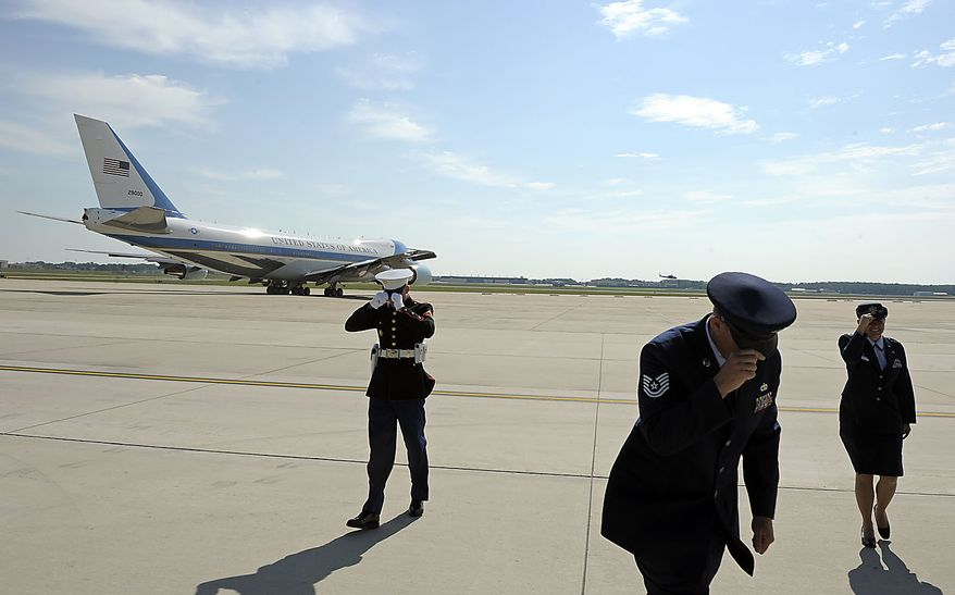 Members of the military hold on to their hats as Air Force One taxis to take-off from Andrews Air Force Base, Md., Friday, July 30, 2010, for a trip to Michigan. (AP Photo/Cliff Owen)