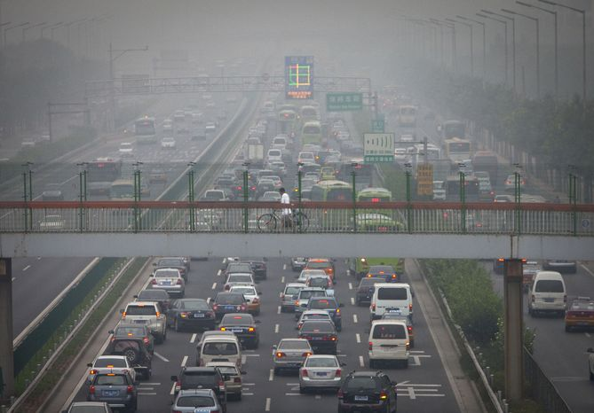 In this July 30, 2010 photo, a man pushes his bike across a pedestrian's overpass while cars heading in town jam on the road during morning commuting in Beijing, China. China is set to overtake Japan as the world's second largest-economy in a resurgence that is changing everything from the global balance of military and financial power to how cars are designed.