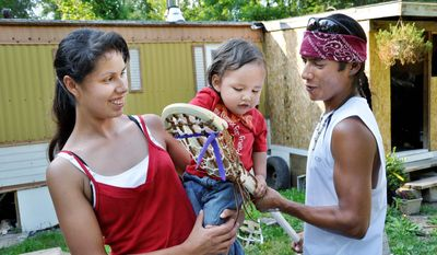 Lacrosse begins at a young age in the Onondaga Nation, where LeeAnne Cornfield and John Parsons interact with their 14-month-old son, Tolli. The sport is a cousin to the medicine games once used to fight off diseases of the white invaders. (Associated Press)
