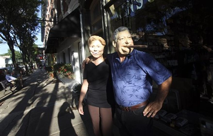 Rhinebeck residents Gary Kiernan, right, and Laurie Bathrick wear Bill and Hillary Clinton masks while walking in downtown Rhinebeck, Thursday, July 29, 2010 in Rhinebeck, N.Y.  (AP Photo/Mary Altaffer)