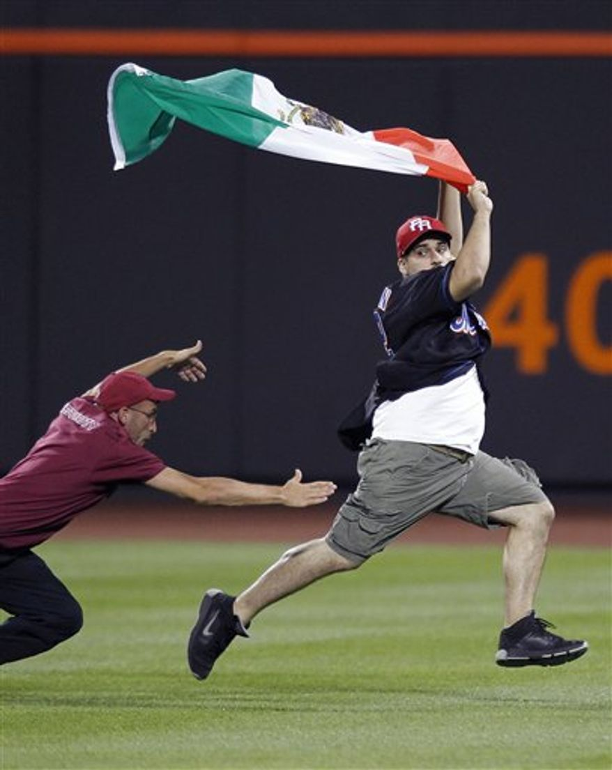 A Citi Field security guard tries to tackle a young man carrying a Mexican flag who ran onto the field in the seventh inning of the New York Mets vs the Arizona Diamondbacks baseball game at Citi Field in New York, Friday, July 30, 2010. (AP Photo/Paul J. Bereswill)