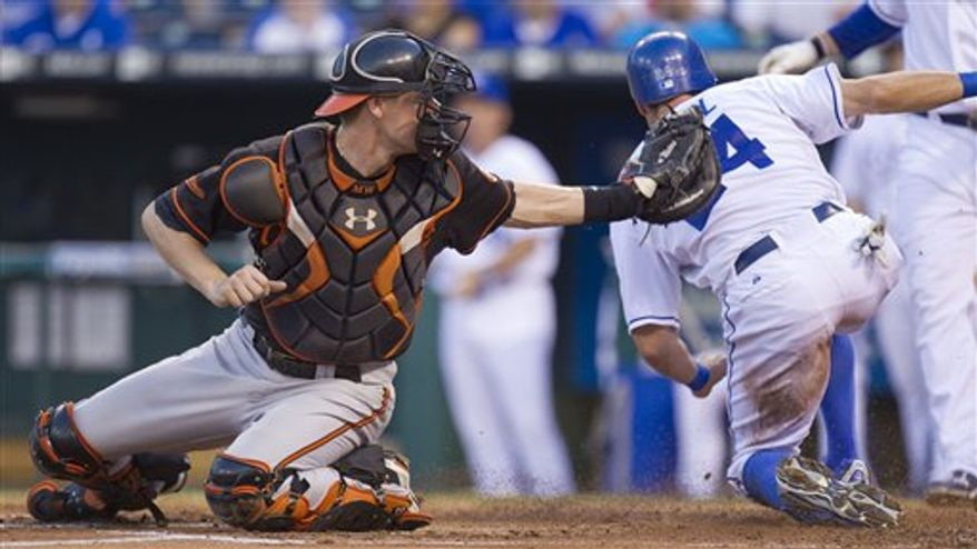 Kansas City Royals' Rick Ankiel, right, beats the tag by Baltimore Orioles catcher Matt Wieters to score on a two-RBI single by Royals' Wilson Betemit during the first inning of a baseball game Friday, July 30, 2010, in Kansas City, Mo. (AP Photo/Charlie Riedel)