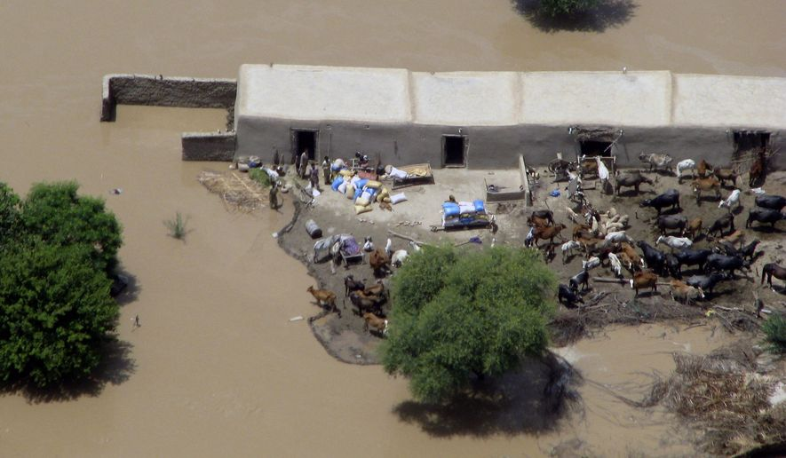 An aerial view shows houses submerged in water because of heavy flooding in Dera Ismail Khan, Pakistan, on Saturday, July 31, 2010. More than 1,100 people have died as rescuers struggle to reach marooned victims and some evacuees show signs of fever, diarrhea and other waterborne diseases. (AP Photo/Ishtiaq Mahsud)