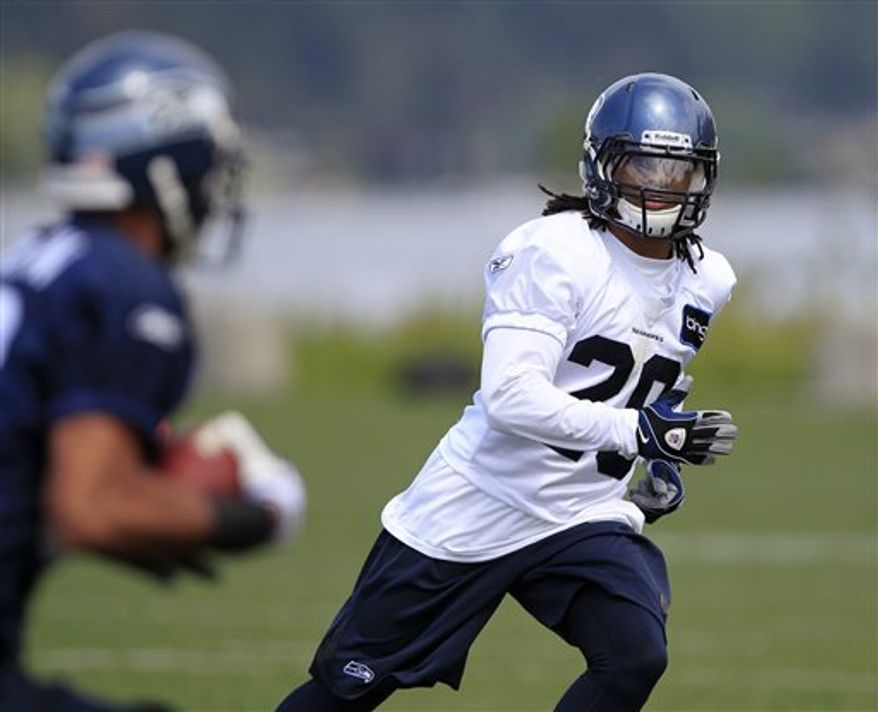 FILE - In this May 24, 2010, file photo, Seattle Seahawks' Earl Thomas, right, tracks a running back during NFL football practice in Renton, Wash. The agent for Thomas, the 14th overall draft pick, said he hopes to have Thomas in camp on time. Seahawks training camp begins Saturday, July 31. (AP Photo/Elaine Thompson, File))