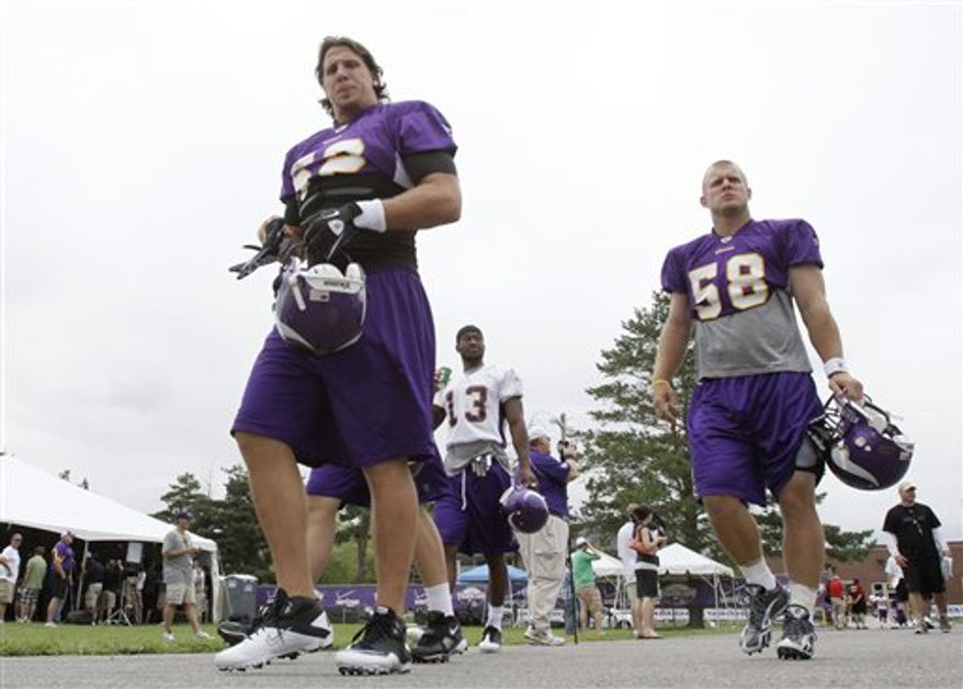 A ballboy lobs a ball as Minnesota Vikings quarterbacks Tarvaris Jackson, left, rookie Joe Webb, center and Sage Rosenfels, right, head to another practice field at the NFL team's football training camp Tuesday, Aug. 3, 2010 in Mankato, Minn., amidst a day of reports that quarterback Brett Favre was retiring  (AP Photo/Jim Mone)