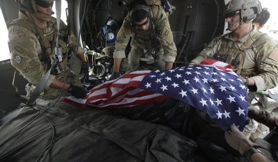 In this photograph made on Thursday, July 29, 2010, upon landing after a helicopter rescue mission, Tech. Sgt. Jeff Hedglin, right, an Air Force Pararescueman, or PJ, drapes an American flag over the remains of the first of two U.S. soldiers killed minutes earlier in an IED attack, assisted by fellow PJs, Senior Airman Robert Dieguez, center, and 1st Lt. Matthew Carlisle, in Kandahar province, southern Afghanistan. July 2010 was the deadliest month for American forces in the nearly 9-year Afghan War. (AP Photo/Brennan Linsley)