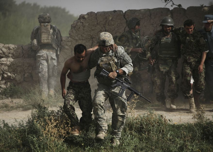 A U.S. soldier helps an Afghan army soldier, one of two wounded in a rocket-propelled grenade attack, to an evacuation helicopter in the Arghandab district of Kandahar province, southern Afghanistan, on Monday Aug. 2, 2010. (AP Photo/Brennan Linsley)
