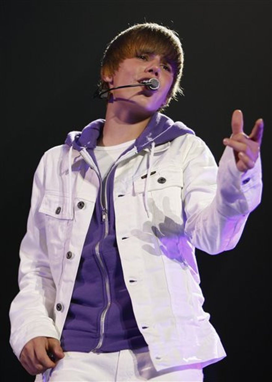 """FILE - In this June 24, 2010 file photo, Justin Bieber performs in Trenton, N.J. On Monday, Aug. 2, 2010, HarperCollins announced that Bieber's book will come out in October 2010. The publisher says """"Justin Bieber: First Step 2 Forever: My Story"""" will reveal the teen sensation's """"amazing journey to stardom."""" The book will include previously unseen photos for """"fans afflicted with Bieber fever."""" (AP Photo/Tim Larsen, File)"""