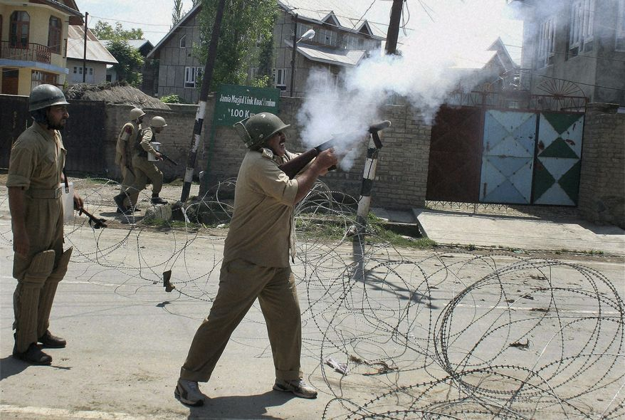 An Indian policeman fires tear-gas shells to disperse protesters during a demonstration defying a curfew in Humhamma, on the outskirts of Srinagar, India, on Monday, Aug. 2, 2010. Government troops fired at thousands of people protesting Indian rule over the country's portion of Kashmir on Monday. (AP Photo)