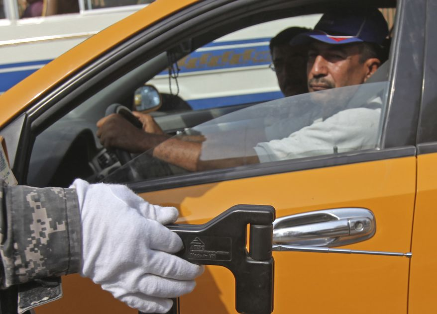 An Iraqi police officer uses a bomb detector at a checkpoint in central Baghdad, Iraq, Monday, Aug. 2, 2010. Two bombings and a drive-by shooting killed eight people Monday, a reminder of Iraq's ongoing instability on a day when President Obama planned to outline progress toward the impending end of U.S. military operations in the country.(AP Photo/Karim Kadim)