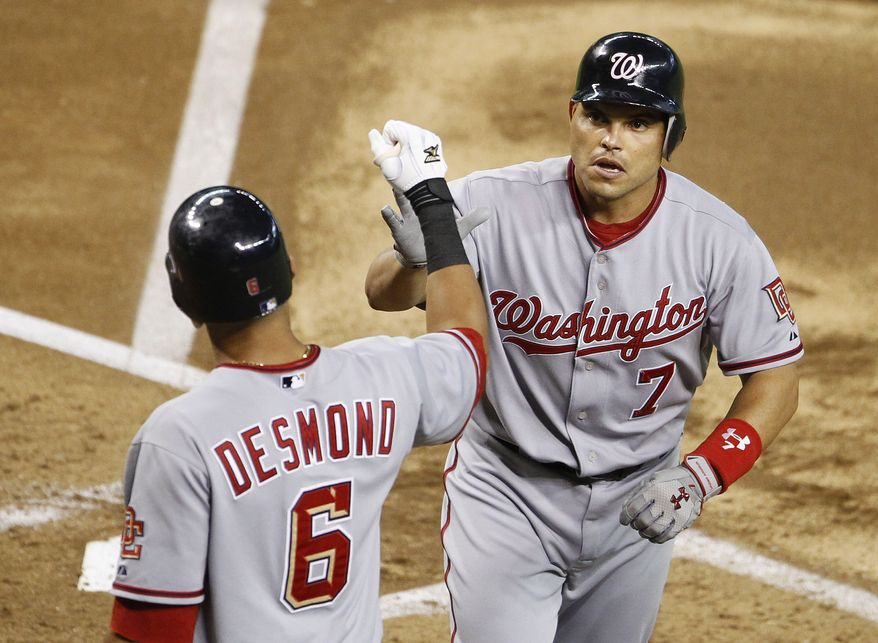 ASSOCIATED PRESS Washington Nationals' Ivan Rodriguez (7) gets a high-five from teammate Ian Desmond (6) after Rodriguez hit a home run against the Arizona Diamondbacks in the second inning of a baseball game Monday, Aug. 2, 2010, in Phoenix. For Rodriguez it was the 300th home run in his career while playing catcher.