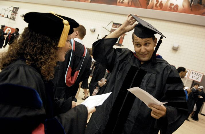 Michelle Leigh Butina, left, watches Sinan Ekrem Gemici, right, adjust his mortarboard hat in one of the waiting rooms in Stegeman Coliseum before they march in the University of Georgia summer commencement exercises in the gymnasium in Athens, Ga., Saturday, July 31, 2010. Princeton Review ranked University of Georgia the No. 1 party school Monday, Aug. 2, 2010. (AP Photo/Kelly Wegel, Athens Banner-Herald)