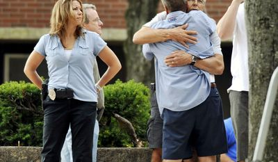 Employees of Hartford Distributors and their families gather at a high school in Manchester, Conn., on Tuesday, after a driver about to lose his job went on a deadly shooting rampage. (Associated Press)