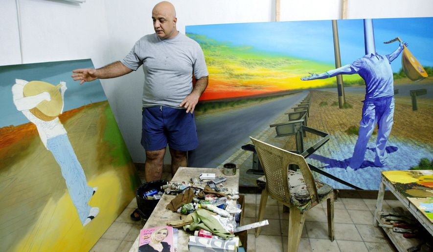 Iraqi painter Muayad Muhsin gestures shows off a painting in his studio in Baghdad. Many of Iraq's artists are using their work to process the turmoil since the 2003 U.S.-led invasion, revealing a profound anger over their country's traumas and uncertainty of its future. (Associated Press)
