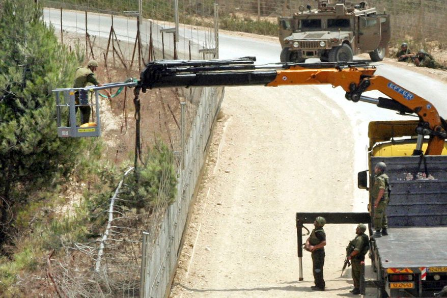 Israeli soldiers use a crane as they cut a tree next to the border fence with Lebanon, near the southern village of Adaisseh, Lebanon, on Tuesday. Lebanese and Israeli troops exchanged fire on the border in the most serious clashes since a fierce war four years ago, authorities said. (Associated Press)