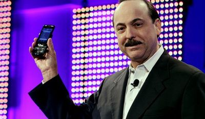 Ralph de la Vega, president and CEO-AT&T Mobility and Consumer Markets, holds the new BlackBerry Torch during a product introduction, Tuesday, Aug. 3, 2010, in New York. (AP Photo/Richard Drew)
