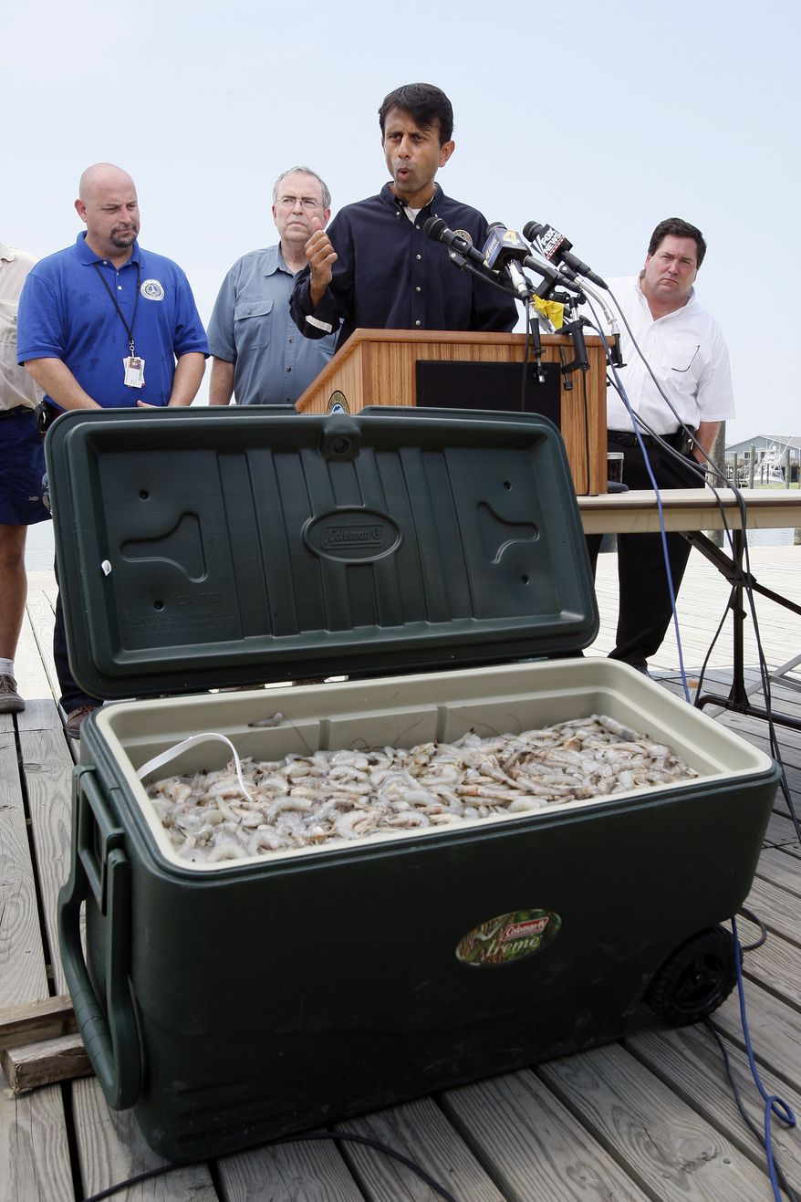 Louisiana Gov. Bobby Jindal, center, speaks at a press conference held to address the reopening of commercial fishing areas along the Louisiana coast behind a chest of shrimp caught this morning in Dixon Bay in Venice, La., Monday, Aug. 2, 2010. Standing behind Jindal are St. Bernard Parish president Craig Taffaro, left, Louisiana Wildlife and Fisheries secretary Robert Barham and Plaquemines Parish president Billy Nungesser. (AP Photo/Patrick Semansky)
