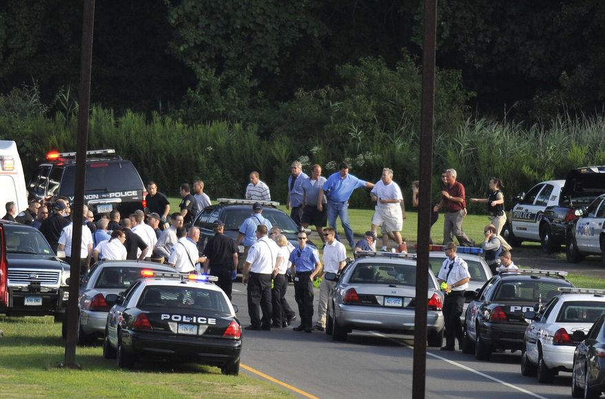 People are seen being evacuated from Hartford Distributors, Inc., in Manchester, Conn., Tuesday, Aug. 3, 2010. Authorities say several people have been shot at the beer distribution company in Connecticut. Police in other surrounding towns and state authorities have been called to the scene. (AP Photo/Journal Inquirer, Jessica Hill)