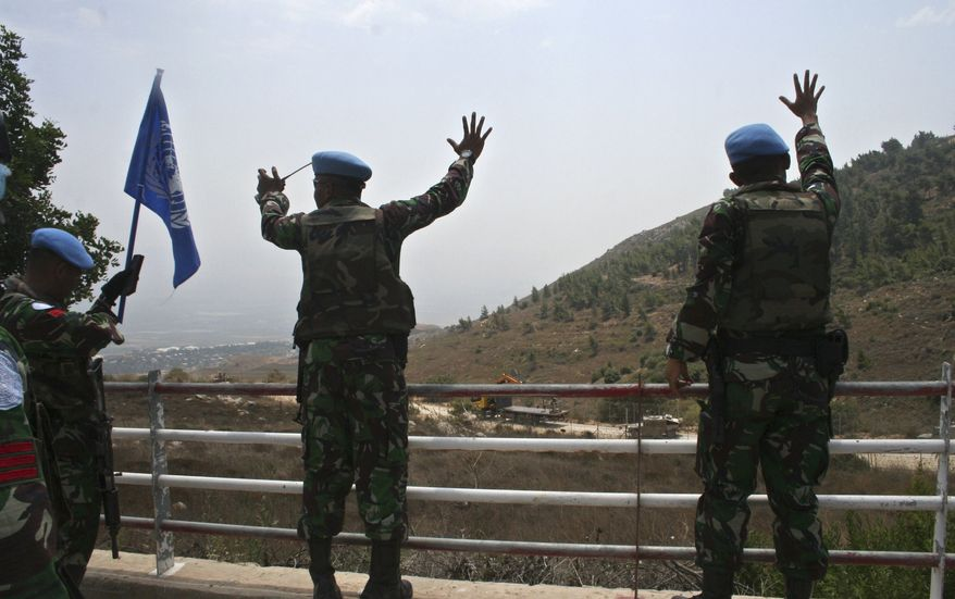 U.N. peacekeepers gesture as Israeli troops patrol the border fence in the southern border village of Adaisseh, Lebanon, Tuesday, Aug. 3, 2010. Lebanon and Israeli troops exchanged fire on the border Tuesday in the most serious clashes since a fierce war four years ago, and Lebanon said at least two of its soldiers were killed in shelling, authorities said. (AP Photo/Lutfallah Daher)