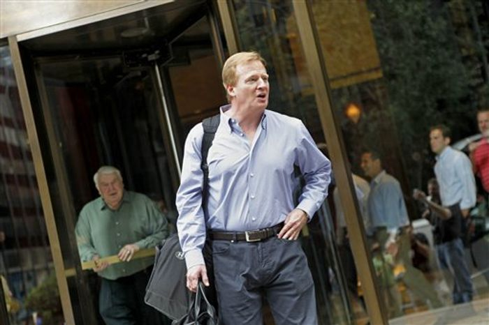 NFL commissioner Roger Goodell, right, and Pro Football Hall of Fame coach John Madden, rear left, leave the NFL offices to board Madden's bus the 'Madden Cruiser, ' to visit training camps, Tuesday, Aug. 3, 2010 in New York. (AP Photo/David Goldman)
