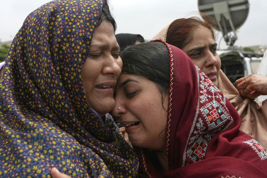 Family members mourn the death of a local leader of the Muttahida Quami Movement Raza Haider in Karachi, Pakistan on Tuesday. Gunmen killed dozens of people in Pakistan's largest city after the assassination of a lawmaker, officials said Tuesday. (Associated Press)